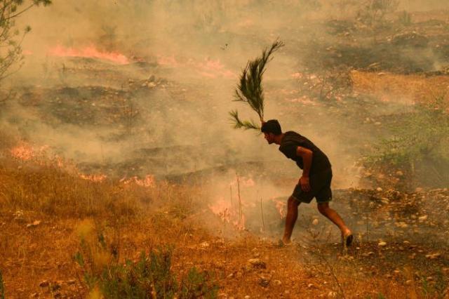 Un homme tente d'éteindre des buissons en flammes, près de la ville de Manavgat, le 29 juillet 2021.