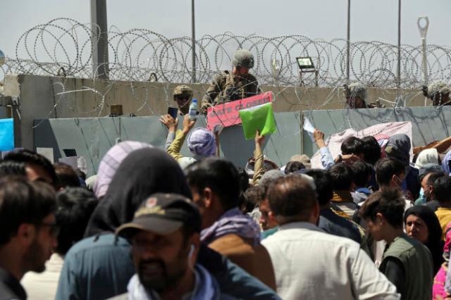 Des Afghans se massent devant les entrées de l'aéroport de Kaboul, en Afghanistan, dans l'espoir d'être évacués du pays, en août 2021.