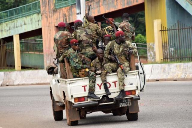 Des membres des forces armées guinéennes traversent le quartier central de Kaloum, à Conakry, le 5 septembre 2021, après que des coups de feu ont été entendus.
