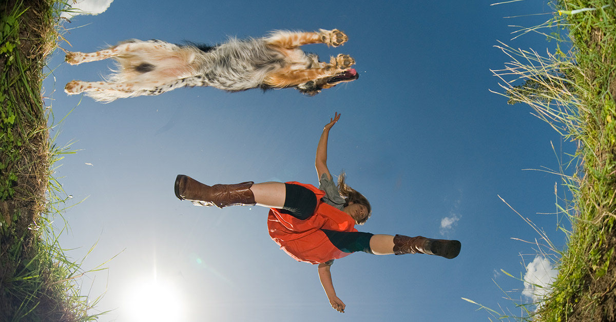 A dynamic view from below of a young woman jumps over a ditch with her sheepdog.