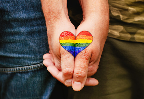 Proud Boys: rainbow heart drawing on hands, LGBTQ love symbol, gay couple hand in hand, homoseaxual lovers
