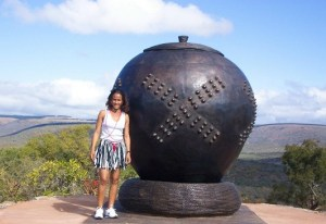 A tourist poses next to the giant khamba pot that marks the view site