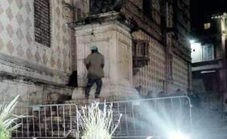 Uomo fa i bisogni sulla statua di Papa Giulio III, sulla scalinata del Duomo