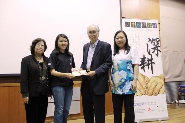 陈凯希在马大中文系主任潘碧华副教授和作协主席拿督曾沛的陪同下,颁发结业证书予小说班班长王婷婷。