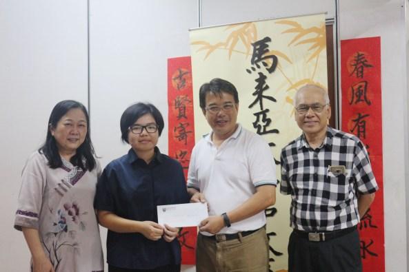 获助学金的学生蔡明意(左二)从侯锦炎先生(右二)手中接获助学金。左一为潘碧华副教授、右为蔡洋踪先生。