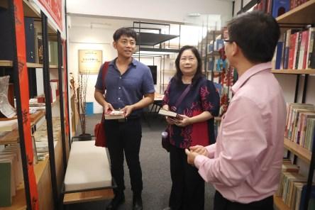研究员谢依伦(右)为来访宾客介绍研究中心藏书。