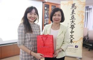 马大中文系高级讲师蔡晓玲博士(左)从驻马来西亚台北经济文化办事处代表洪慧珠女士(右)手中接过纪念品。