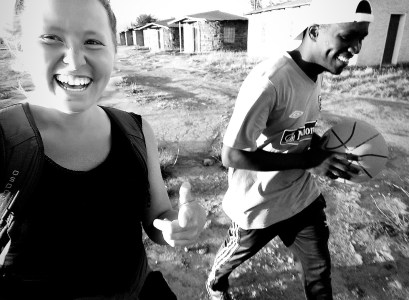 "Caroline ""Carrie"" Maggio, who studied art history at UMW and now a Peace Corps volunteer, walks with a basketball player in Lesotho, South Africa."