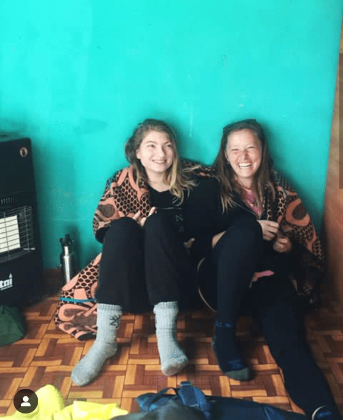 "Caroline Maggi (right) sits with a friend in Lesotho, South Africa, where she is a healthcare volunteer for the Peace Corps. After a long day, Maggio said, ""watching the sun slip behind the mountains ... puts the biggest smile on my face."""
