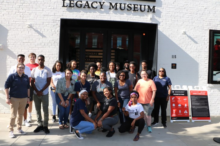 Mili Mehari (front row, far right) poses with UMW students who joined the first-ever Fall Break Social Justice trip to Alabama stand in front of the Legacy Museum in Montgomery. Mehari played an important role in making the trip possible, including securing funds.