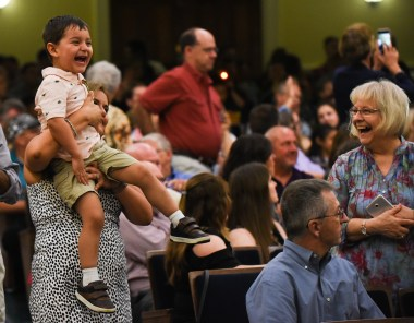 Liam Skinner laughs as his father, Chris Skinner, enters Dodd Auditorium at the start of the UMW Graduate School graduation ceremony.
