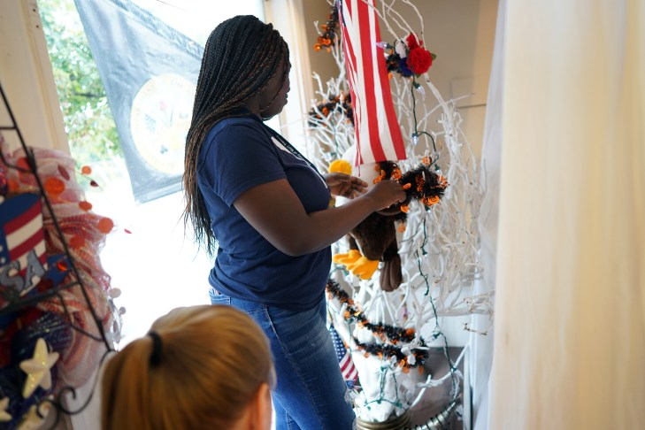 Bridget Gyamfi helped decorate the windows at MANARC Veterans' Thrift Store in downtown Fredericksburg. Photo by Suzanne Carr Rossi.