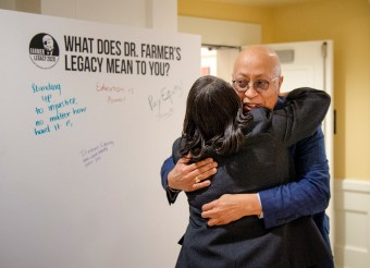 "James Farmer Multicultural Center Director Marion Sanford hugs Xavier Richardson at the launch of UMW's Farmer Legacy 2020 celebration. Attendees were asked to sign boards asking the question, ""What does Dr. Farmer's legacy mean to you?"" Photo by Tom Rothenberg."