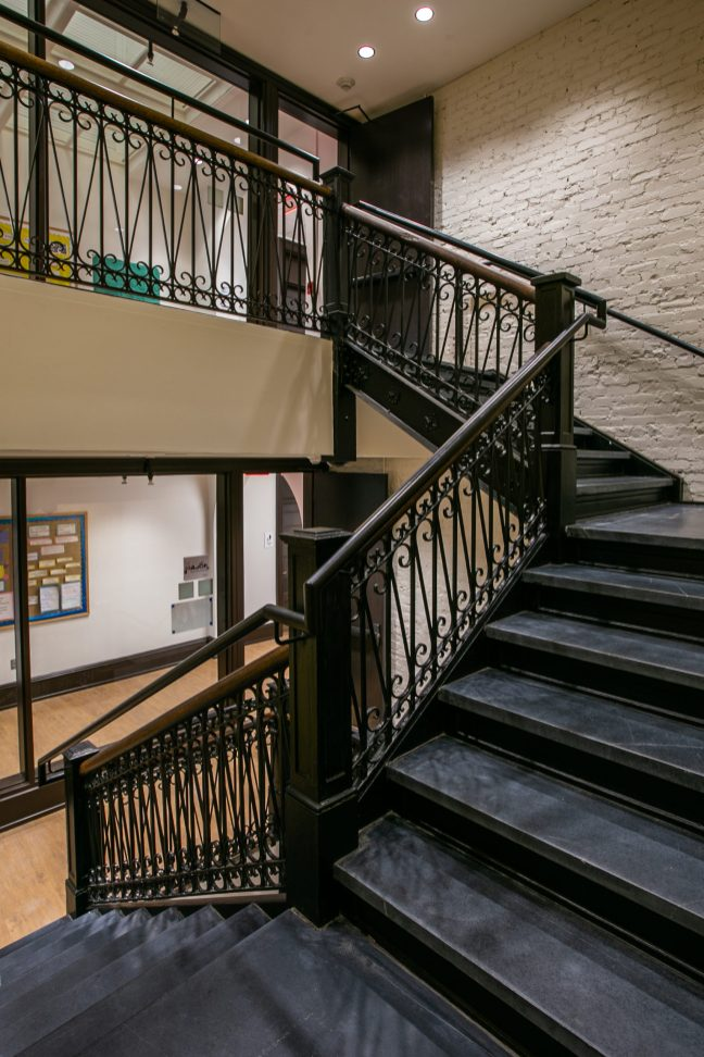 Original iron banisters and brick walls are among the details that were preserved in the recent Willard Hall renovation. Photo by Craig Hutson, Kjellstrom and Lee Construction.