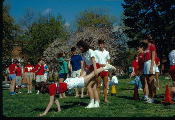 """Students participate in a """"wheelbarrow race"""" for Devil Goat Day on the lawn in front of Jefferson and Combs Halls in 1985. Photo courtesy of Simpson Library Special Collections."""