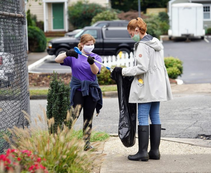 From left to right: Emma Bradley and Katherine Lauderbaugh pick up trash in Kenmore Park on Saturday morning. Photo by Suzanne Carr Rossi.