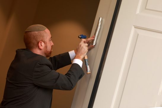 Rabbi Menachem Sherman, the Center director, hammers a mezuzah on the doorpost, which serves as a reminder that homes are holy places and those that enter should act accordingly. Photo by Karen Pearlman.
