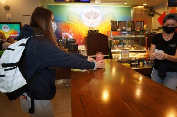 Donning a Mary Washington mask from the UMW bookstore, freshman Lexi St. Clair picks up a smoothie in Katora Cafe. Photo by Suzanne Carr Rossi.