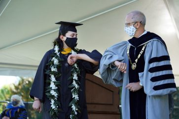 UMW President Troy Paino elbow bumps Gabi Radoiu '20 as she crosses the stage. Handshakes were out this year due to the pandemic. Photo by Suzanne Carr Rossi.