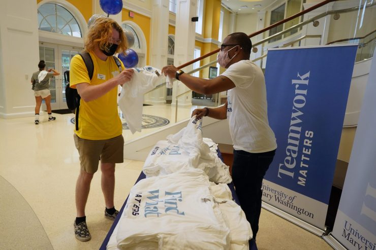 """Orientation Coordinator Joey Zeldin grabs a """"Find What Matters"""" T-shirt from Director of University Marketing Malcolm Holmes in the University Center. Photo by Suzanne Carr Rossi."""