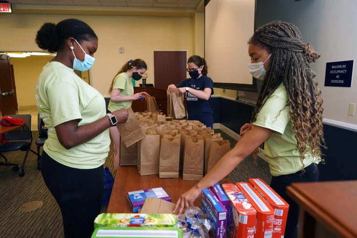 From left to right, Aniya Stewart, Michelle Snellings, Kaylee Deardorff and Cassidy Richardson assemble lunches for Micah Ecumenical Ministries. Photo by Suzanne Carr Rossi.