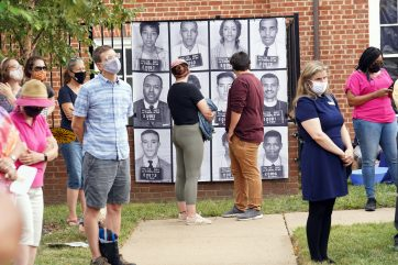 Onlookers gaze at the banner featuring the mug shots of the original Freedom Riders, including the late Dr. James Farmer (first photo in second row) and the late Rep. John Lewis (fourth photo in third row). Photo by Suzanne Carr Rossi.