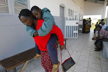 A woman carries her son from a Mozambican health clinic