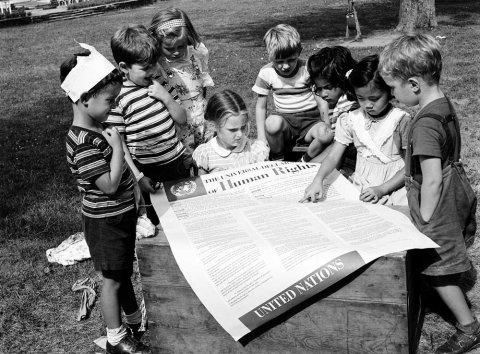 Foto ONU En 1950, en el segundo aniversario de la adopción de la Declaración Universal de los Derechos Humanos, los estudiantes de la Escuela Infantil Internacional de la ONU en Nueva York vieron un cartel del documento histórico.