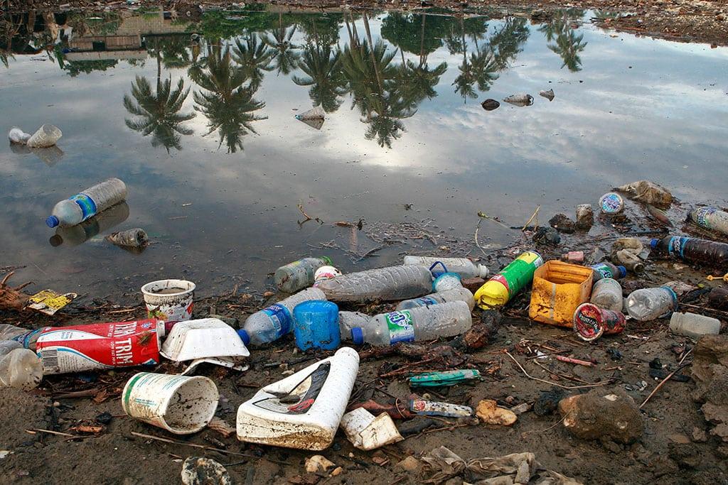 Botellas de plástico y restos de la basura de un pueblo cercano flotan en la orilla de un río. Después se verterán en el mar. Foto: ONU/Matine Perret