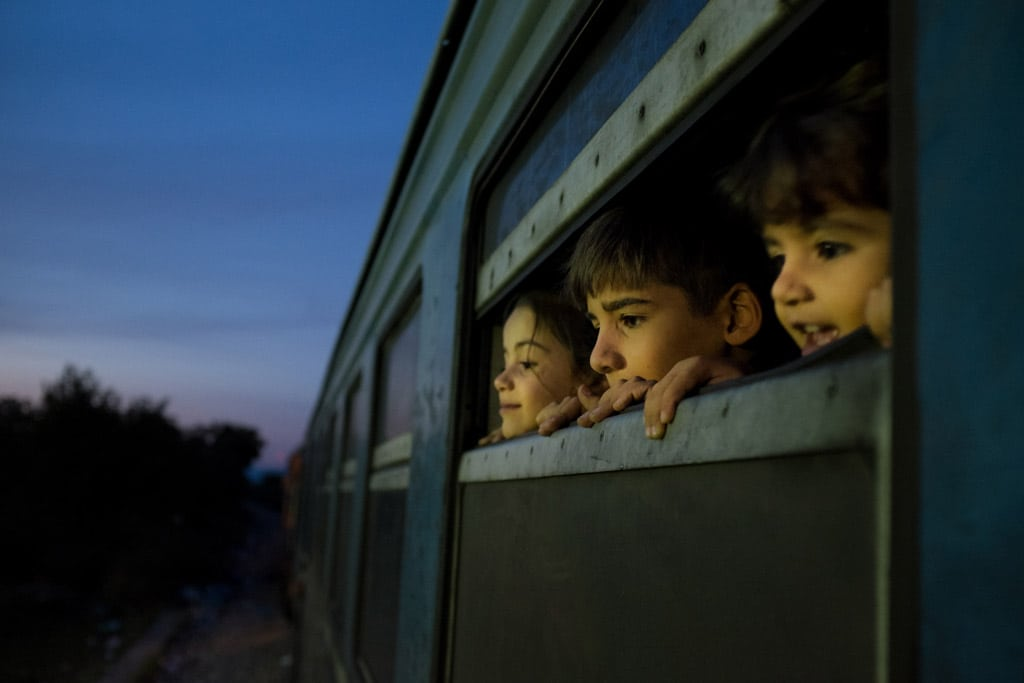 Photo: Children look out a train window at a reception centre for refugees and migrants in the former Yugoslav Republic of Macedonia.