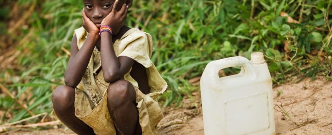 Photo: A little girl waits to fill her water container in the village of Kikonka, Bas-Congo province, Democratic Republic of Congo.