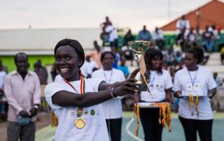 Photo: A young woman from a volleyball team poses with her medal at a special event held today in Juba, South Sudan, in celebration of the International Day of Sports for Development and Peace.
