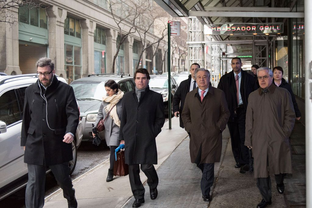 Mr. Guterres (centre right) on his way to UN Headquarters for his first day at work as Secretary-General on 3 January 2017. UN Photo/Mark Garten