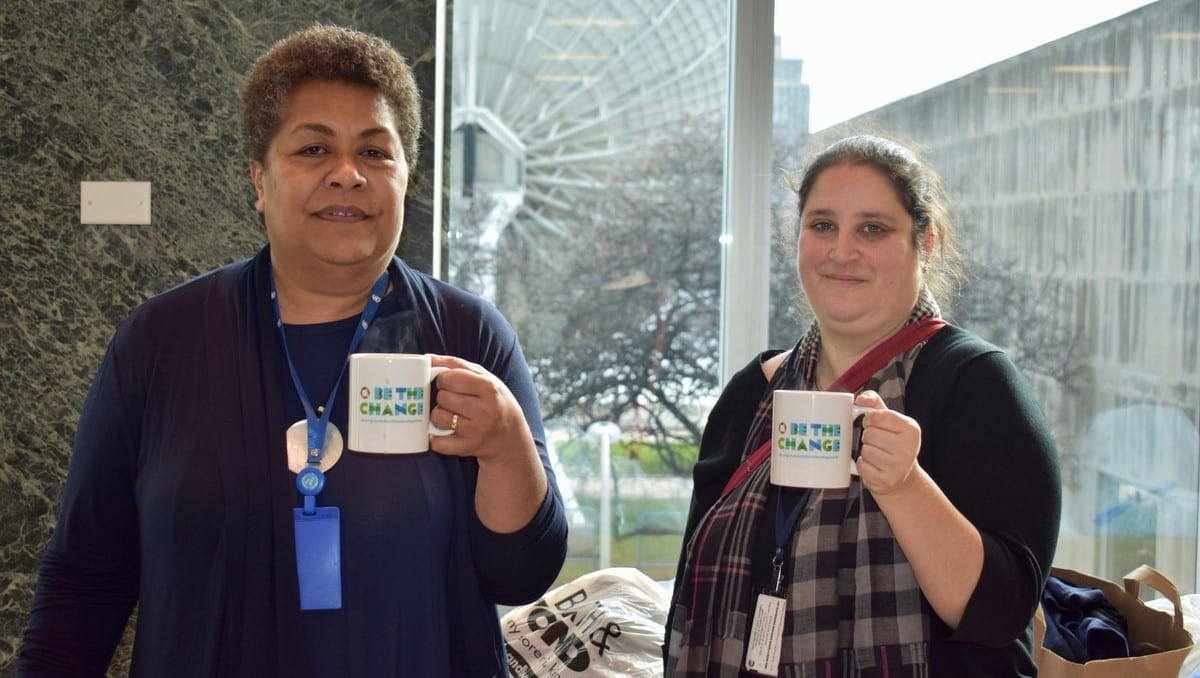 """UN staff in New York holding """"Be the Change"""" mugs"""