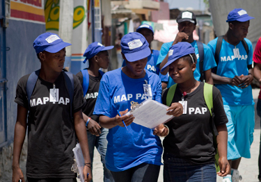 Participants in the Voices of Youth Maps initiative wearing T-shirts with the slogan ''MAP PAP'' (Port-au-Prince) as they walk on a street in the Village de Dieu neighbourhood.