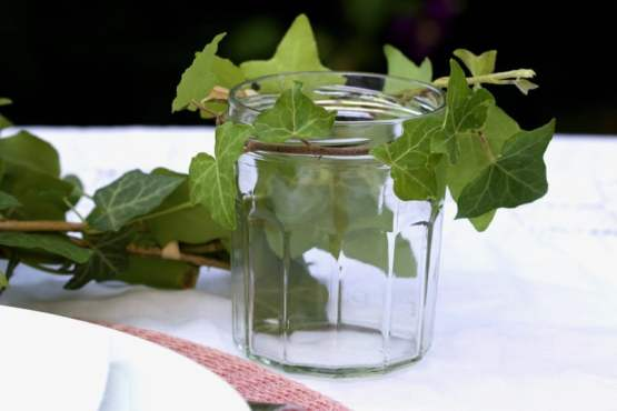 Lierre et pots de confiture pour une table d'été romantique au jardin.