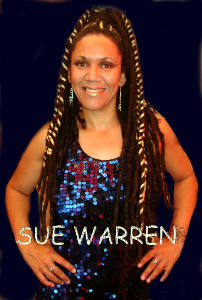 Photo of Sue Warren, singer. A smiling woman with long dreadlocks, in a blue-sequined sparkly dress.