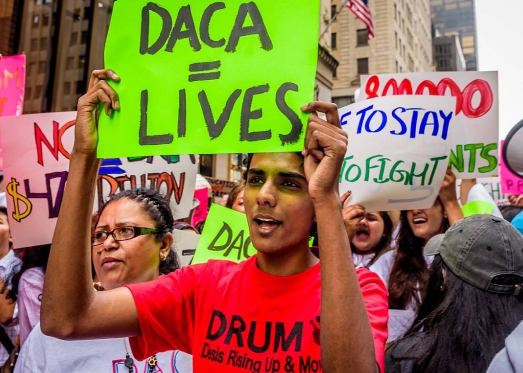 Young people protesting in favor of DACA, with the person in front holding a sign that reads DACA = Lives.