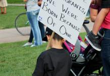 A child holds a sign in support of immigrants at UNC's Dreamers Without Borders Rally
