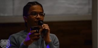 Poet featured in photo next to microphone reading off his phone in his hand.