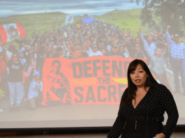 Matika Wilbur stands in front of her visual presentation