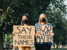 """Two young women stand with signs, one saying """"Say their names,"""" the other saying """"Black Lives Matter."""""""