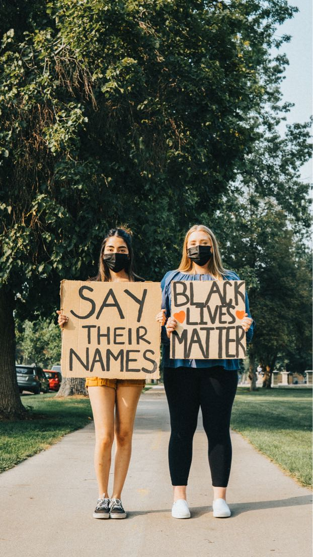 Two young women stand with signs, one saying