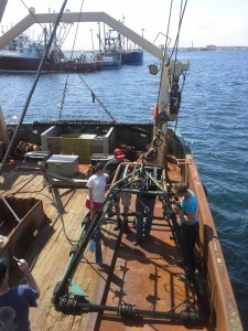 Scientists and students from UMass's School for Marine Science and Technology (SMAST) load the DropCam on board a fishing vessel in preparation for a video survey research cruise.