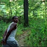 African American teenage boy with his hands tied togethre runs for his life through the woods