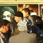 Iraqi citizens walk in an open Iraq market in Kadhimiya