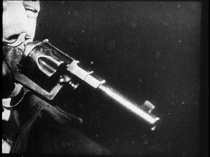 Close-up of a man pointing a gun