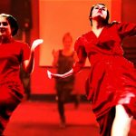Two teenage girls wearing red dresses perform a modern dance