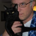 Filmmaker Jeff Krulik holds his black cat Iggy up to his face