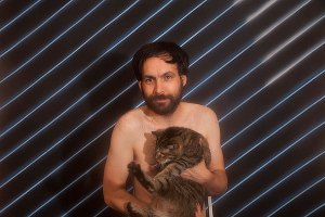 Naked Mike Olenick cradles his striped cat Crystal